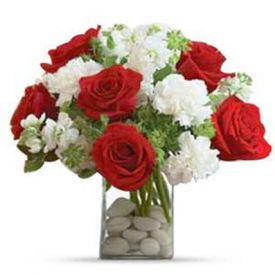 Red roses and white carnations with greens arranged in a glass vase