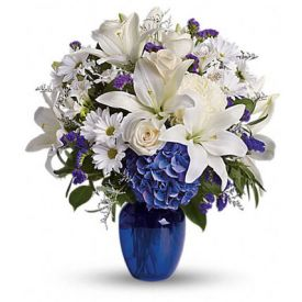 beautiful bouquet pairs pure white flowers with deep blue blooms in a gorgeous blue glass vase