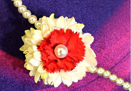 Pretty rakhi with fresh red carnation