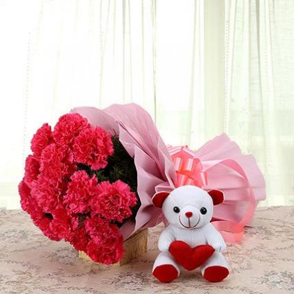 A bunch of Red carnations, and white cute teddy bear